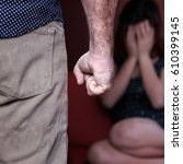 Small photo of Domestic or gender violence - Aggressive man with a clenched fist threatens to hit a scared woman