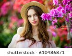 Stock photo close up portrait of a beautiful girl in a pink vintage dress and straw hat standing near colorful 610486871