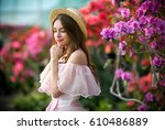 Stock photo beautiful girl in pink vintage dress and straw hat standing near colorful flowers art work of 610486889