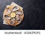 opened oysters and lemon over... | Shutterstock . vector #610629191