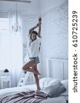 Small photo of Spending carefree time. Full length of playful young woman keeping arms raised while standing on the bed at home