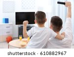 father and son watching sports... | Shutterstock . vector #610882967