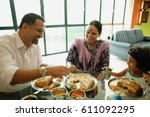 family of three having a meal... | Shutterstock . vector #611092295