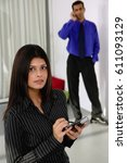 Small photo of Businesswoman with PDA, looking up at camera, man in the background, using mobile phone
