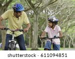a father and son ride their... | Shutterstock . vector #611094851
