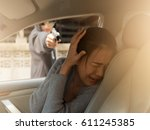 Small photo of A woman scared robber dressed in black looking and pointing a gun at a woman driver in a car ,Dangerous man ,Fear ,Murder, hijack,rape and crime concept