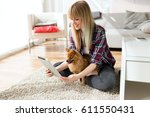 Stock photo portrait of beautiful young woman with her dog using digital tablet at home 611550431