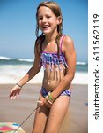young girl playing on the beach ... | Shutterstock . vector #611562119