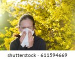 Small photo of Young girl blowing nose and sneezing in tissue in front of blooming tree. Seasonal allergens affecting people
