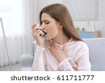 Small photo of Young woman using asthma inhaler at home