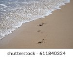 footprints in the sand with wave | Shutterstock . vector #611840324