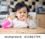 asian baby girl eating toasted... | Shutterstock . vector #611861744