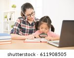 Small photo of asian pretty mom carefully accompany sweet little daughter study with enlarger in the living room in holiday. beautiful children using magnifier.