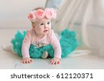 Small photo of Image of sweet baby girl in a wreath of pink roses, closeup portrait of cute 8 month-old smiling girl, toddler