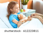 Doctor and little patient with teddy bear holding hands in hospital  - stock photo