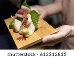 hand holding fresh sashimi on a ... | Shutterstock . vector #612312815