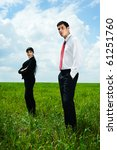 serious businesspeople standing on green meadow over blue sky - stock photo