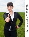 Happy businesswoman showing thumbs up sign over green meadow - stock photo