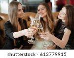 cheerful girls clinking glasses ... | Shutterstock . vector #612779915