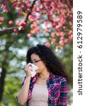 Small photo of Young woman sneezing and blowing nose in tissue in front of blooming tree. Seasonal allergens affecting people