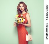 Small photo of Blonde young woman in elegant red dress. Girl posing on a green background with handbag. Jewelry and hairstyle. Lady with spring bouquet of flowers. Fashion photo