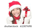 Santa woman showing gift wearing Santa hat. Christmas woman portrait of a cute, beautiful smiling mixed Asian / Caucasian model. Isolated on white background. - stock photo