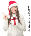 Christmas woman pointing up to the side at copy space. Isolated on white background. Beautiful young smiling woman in Santa hat and sweater showing empty copyspace. Asian / Caucasian female model. - stock photo