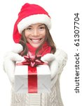 Christmas gift woman smiling holding present isolated on white background. Santa girl in winter sweater showing gift wearing Santa hat. Cute, beautiful model: mixed Asian / Caucasian. - stock photo