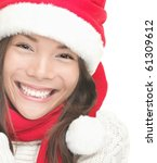 Christmas woman smiling portrait. Young woman wearing Santa hat, sweater and red scarf. Closeup photo of cute Asian / Caucasian woman isolated on white background - stock photo