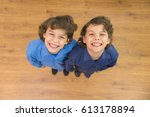 The two twin kids smile to the camera. View from above