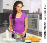 young cooking woman at kitchen | Shutterstock . vector #613238117