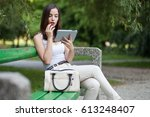 young woman using tablet in park | Shutterstock . vector #613248407