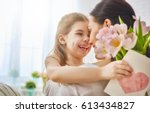 Small photo of Happy mother's day! Child daughter congratulates mom and gives her flowers tulips and postcard. Mum and girl smiling and hugging. Family holiday and togetherness.