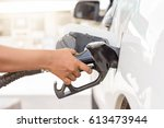 Stock photo the woman s right hand holds the nozzle to refuel the white car 613473944