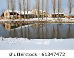 Old country house covered of snow in winter with trees reflecting on the river, Po valley, Italy - stock photo