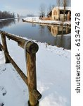 River and old country house covered of snow in winter, Po valley, Italy - stock photo