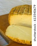 Small photo of cut head of traditional Adygei cheese handmade on wooden Board