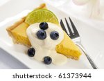 Lemon tart topped with fresh cream, blueberries and lime.  Delicious! - stock photo