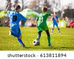kids kicking soccer ball on... | Shutterstock . vector #613811894