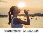 sporty woman drinking water...   Shutterstock . vector #613864235