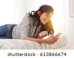 Small photo of Young cheerful woman lying on bed shuffling songs on mobile phone. Relaxed girl listening music with headphone at home. Happy woman in casual enjoying music in bedroom while texing a message phone.