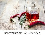 bottle with chili oil and herbs ... | Shutterstock . vector #613897775