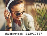 happy young woman listening to... | Shutterstock . vector #613917587