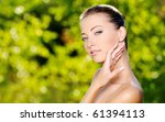 Beautiful sexy face of an young woman with fresh health skin. Female posing on the nature. Model stroking her body. - stock photo