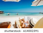 woman on sunbed reading book... | Shutterstock . vector #614002391
