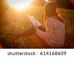 Girl Reads In Sunset