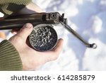 Small photo of A man in a camouflage jacket holding a BB gun and a box of buckshot, ammunition. Man charged windbreaker in winter snow-covered forest.