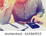 man counting using calculator... | Shutterstock . vector #614364515