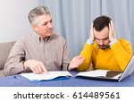 Small photo of Adult father and son discuss difficult and serious contract at home