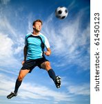 Male football player heading the ball in the air - stock photo